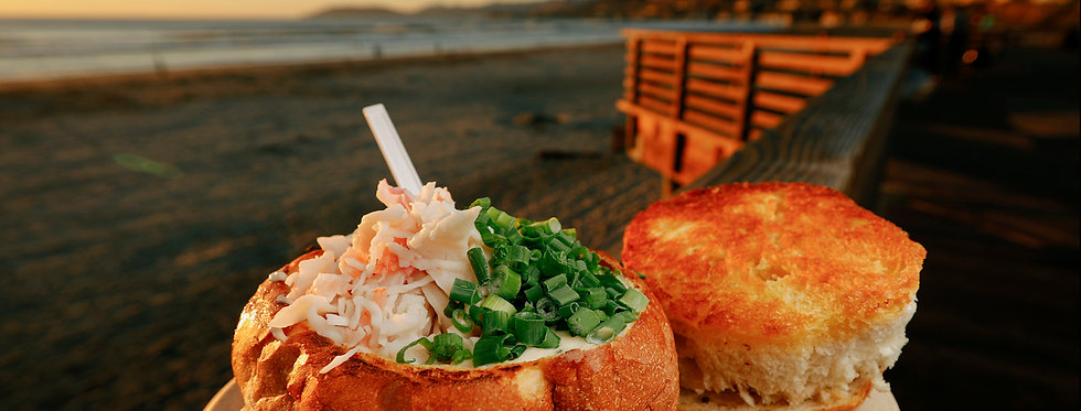 Sourdough bread bowl filled with clam chowder and toppings of seafood and green onions sitting on the Pismo Pier at sunset