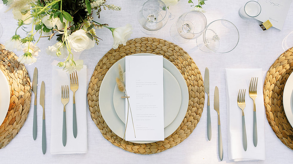 Overhead view of elegant place setting on a white table cloth with wine glasses and gold flatware