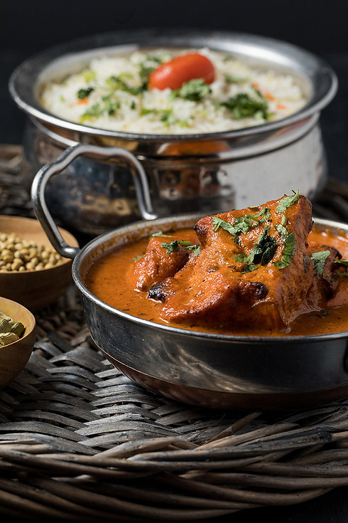 Bowl of hot, spiced chicken tikka masala with a bowl of spiced white rice in the background