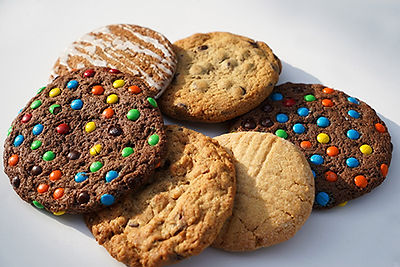 Variety of freshly baked cookies: chocolate chips, M&Ms, icing, peanut butter, sugar