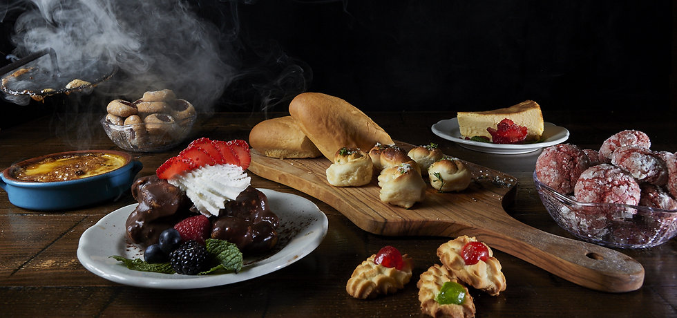 Table featuring steaming fresh baked bread, garlic bread knots, chocolate-dipped profiteroles, cheesecake and Italian cookies
