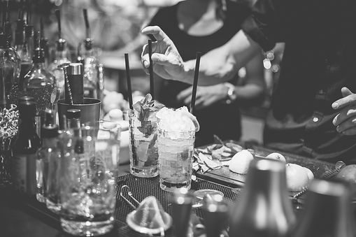 Cocktails being made at a bar, glasses chilling with ice, mint springs added for garnish