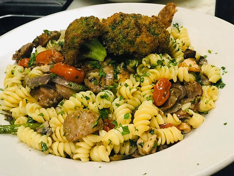 Sarda with Truffle Oil dish - fusilli pasta, Italian sausage, tomatoes, asparagus, basil, green peas, cremini mushrooms, garlic, cauliflower and truffle oil