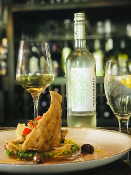 Bottle of chilled white wine with a glass of white wine paired with a crispy fish dish