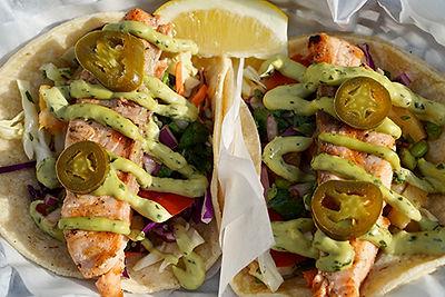 Grilled salmon tacos prepared Baja Style with slaw, tomato, jalapeños, citrus salsa, avocado ranch sauce, and raucous daucus aioli