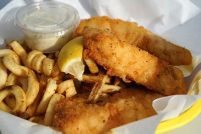 Golden fried fish and curly fries with tartar sauce and a lemon wedge