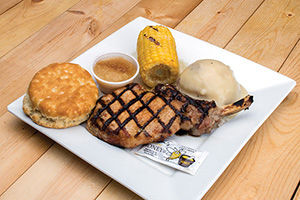 Grilled pork chop with mashed potatoes, corn on the cob, and biscuit