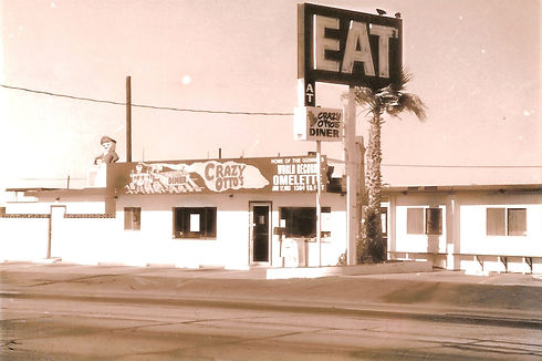 """Close-up black and white photo of original restaurant on Sierra Highway in the 1970s; big """"EAT at Crazt Otto's Diner"""" sign"""