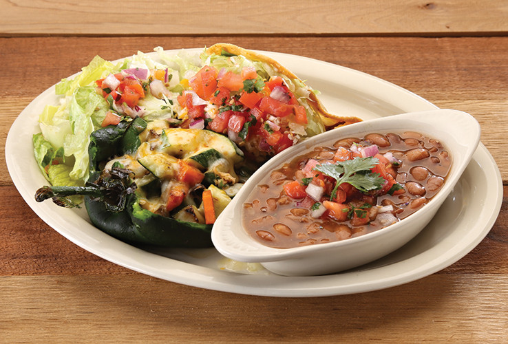 Fresh stuffed pepper, taco, and dish of hot beans on a platter with rustic wood background
