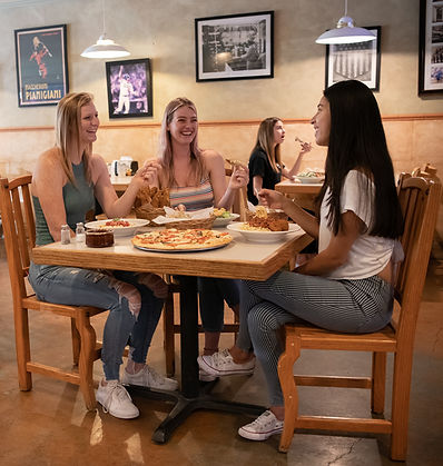 3 Young Women Enjoying Pizza and Salad While Talking and Laughing