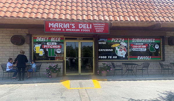 Exterior of Maria's Deli, specials painted on windows, outdoor seating