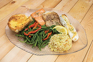 Seafood Sampler, with halibut, salmon, sea bass, rice, green beans, and garlic bread