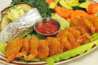 Fried shrimp with sauteed vegetables and a baked potato