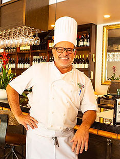 Chef/Owner Dario Furlati in chef's attire, smiling, casually leaning against bar