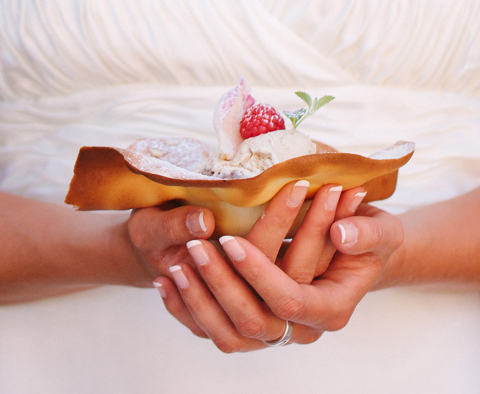 A lady's nicely manicured hands holding a dessert pastry shell fill with ice cream and fresh fruit