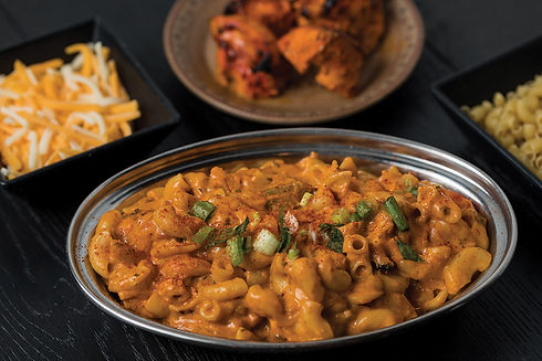 CTMAC 'n Cheese topped with spices, cheese and chicken tikka masala in the background