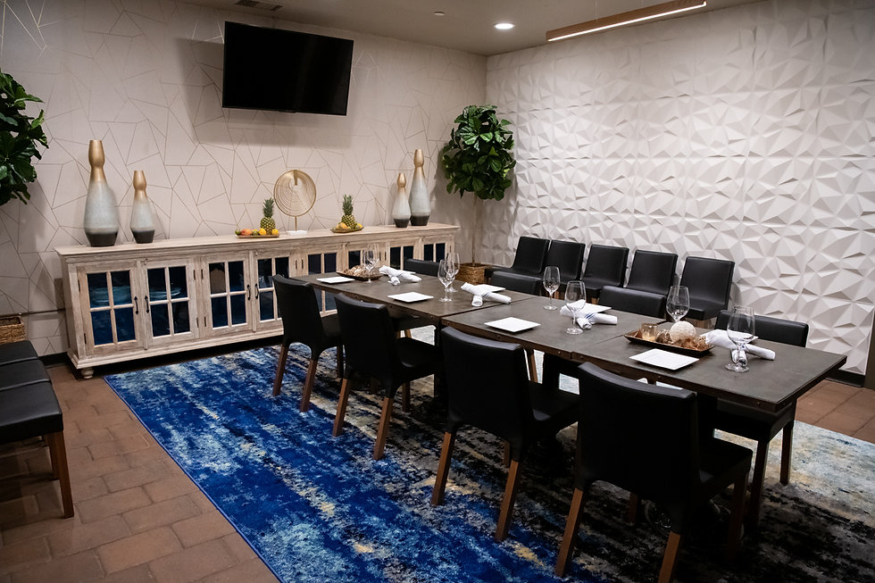 Spacious private dining room with geometric textured wall, large flatscreen TV, elegant modern furniture and decor