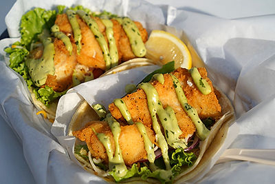 Fried fish tacos made Classic style with lettuce, tomato, onion, cheese and avocado ranch sauce