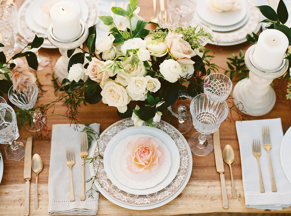 Overhead view of beautiful wood table with gold flatware, intricate china dishes, water goblets, roses and greenery