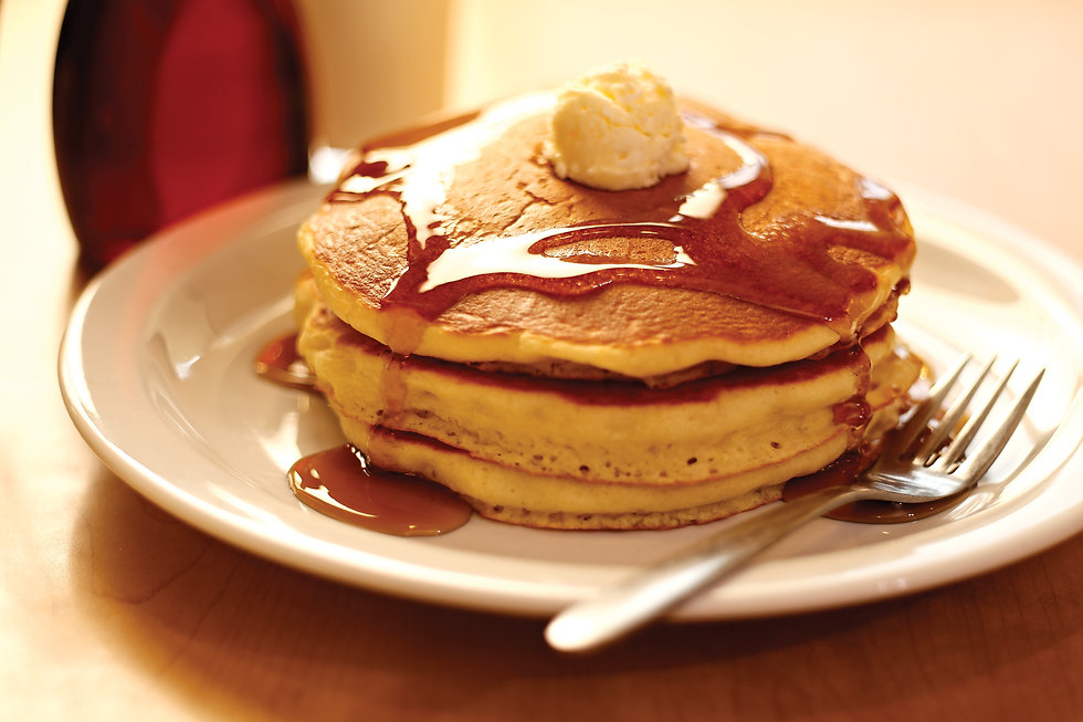 A plate of stacked fluffy pancakes with butter and drizzled syrup