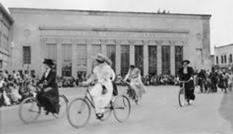 Black and white photo of women in Victorian dresses and hats riding bikes through a plaza
