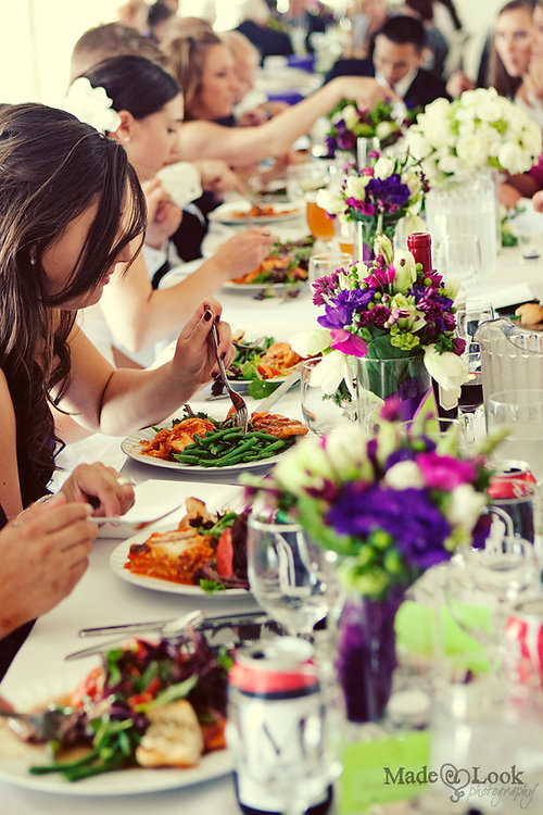 A long table at a wedding reception, bright flowers down the center, guests dining on plated dinners