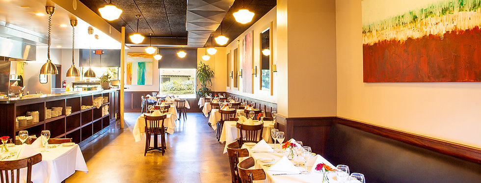 Goleta location dining area with dark wood accents and vibrant art, and tables with white tablecloths and napkins