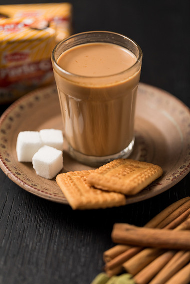 Chai with biscuits and sugar cubes