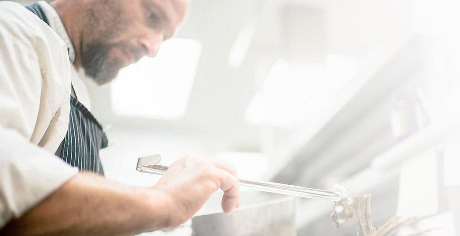Chef Nicola spooning sauce onto a dish