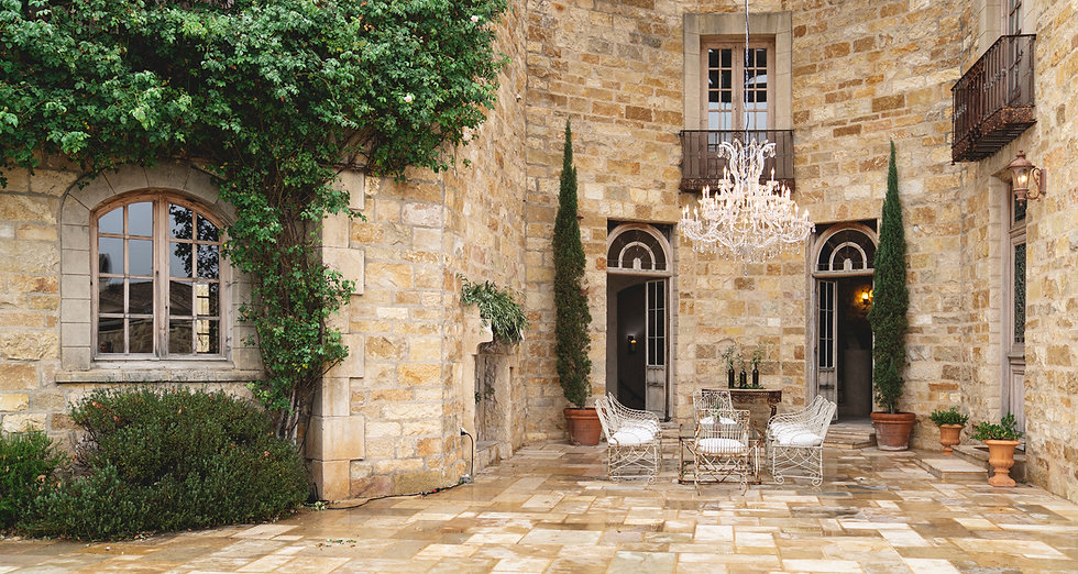 A stone patio at Sunstone Winery Estate in Santa Ynez, trees and shrubs growing up the stone walls, dazzling chandelier hanging above chairs on the patio