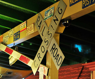 Railroad crossing sign, crossing guard, and old license plate decor