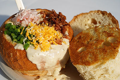 Bread bowl overflowing with clam choder, topped with cheese, bacon, green onions, and seafood