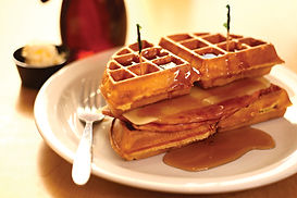 Ham and cheese sandwiched between waffle quarters, drizzled with syrup