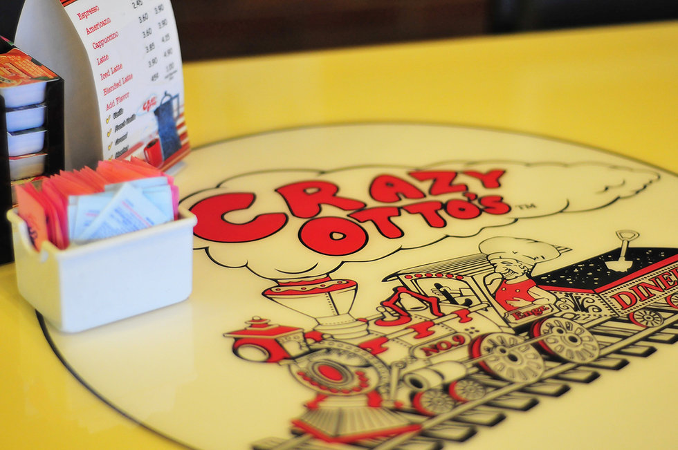 Dining table with Crazy Otto's logo, sugar packets, jams and jellies