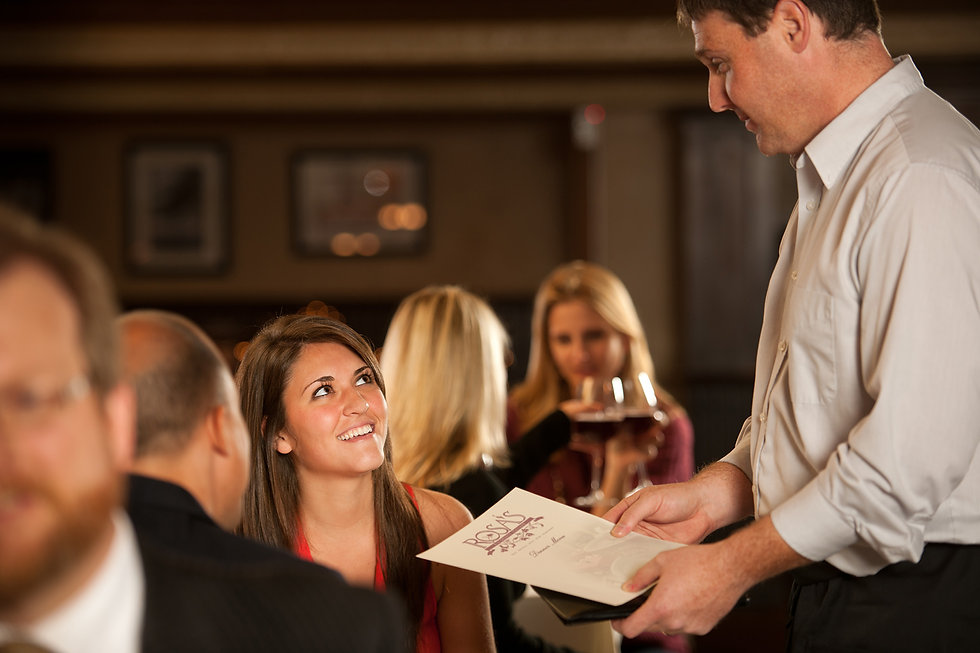 Woman looking up at male server holding a restaurant menu