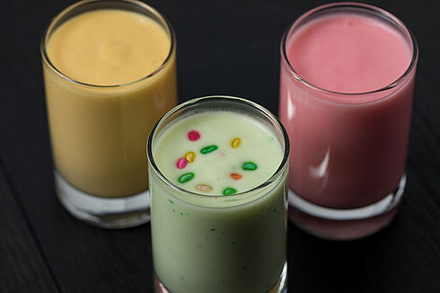 A trio of lassi flavors, colored yellow, pink and green