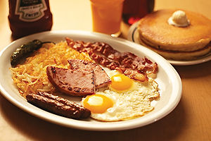 Sammy's Big Breakfast with fried eggs, hash brows, pancakes, bacon, sausage and ham