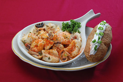 Sautéed Combo with mixed seafood in garlic butter and wine, with a baked potato on the side topped with sour cream and chives