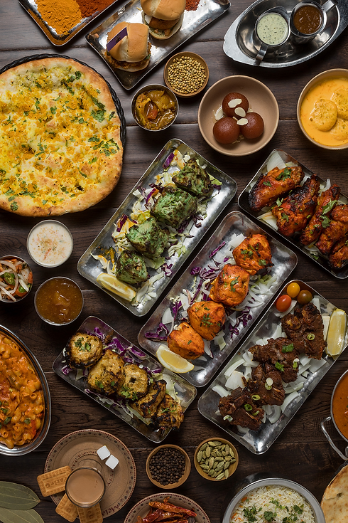 Array of colorful dishes including naan, kebobs, desserts, chutneys, tandoori chicken, and spices
