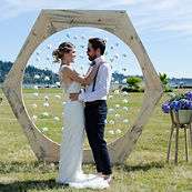 Couple says I Do on waterfront property at Bellingham Bay; Homemade arbor with floral garlands