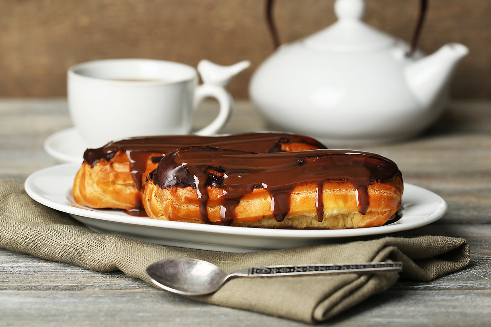 Tasty eclairs and cup of tea on wooden t