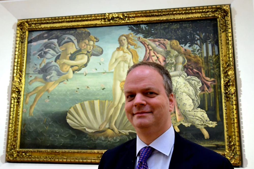 Eike Schmidt, director of Uffzi Gallery, poses in front of The birth of Venus (circa mid 1480s) by Sandro Botticelli during a press preview for the reopening of the rooms dedicated to Pollaiolo and Botticelli, at the Uffizi Gallery in Florence, on October 17, 2016. Photo Alberto Pizzoli/AFP/Getty Images. Artworks Advisory