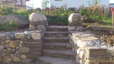 Single dry stone retaining walls and steps Built entirely with recycled stone from the site this dry stone entrance compliments the self-built eco house nicely.