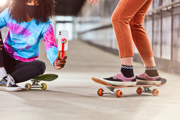 Girls filming skating in a tunnel with a Popsocket and Iphone