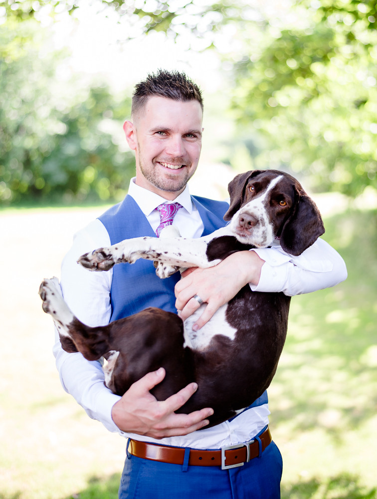 Groom and dog at wedding