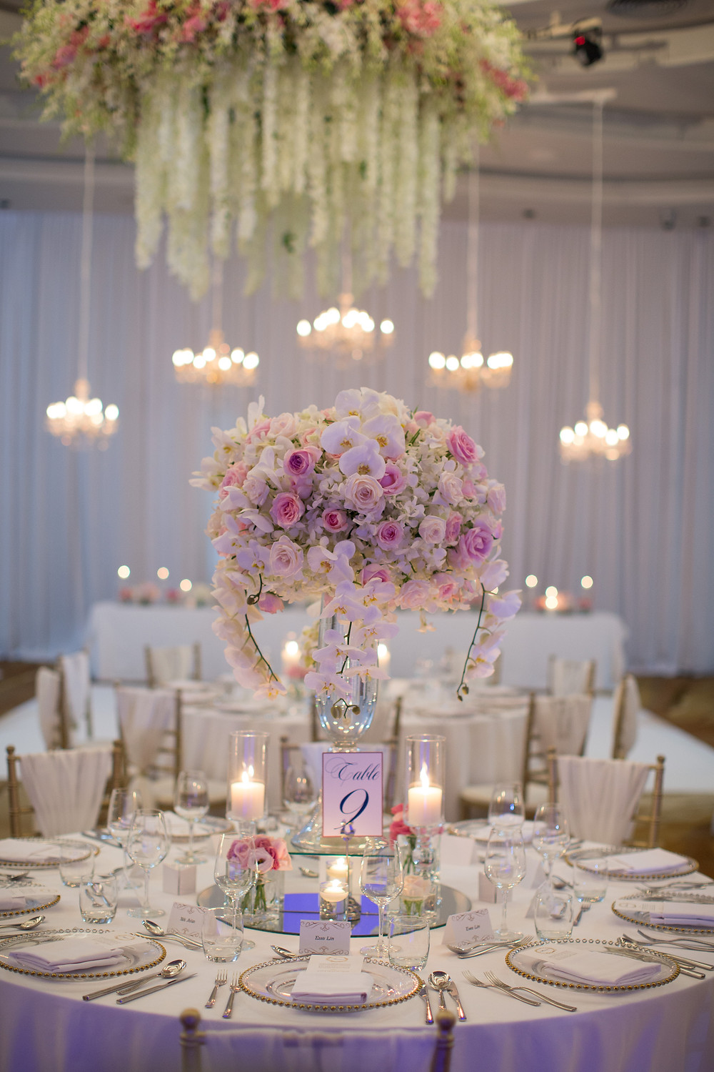 The Dinner Reception ,Flower Centerpiece and Candle light orchids, rose, flow over from the tall vase.