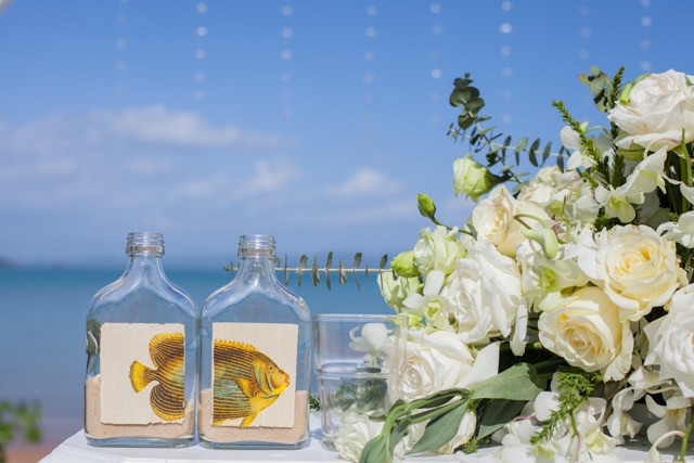 The Ceremony sand created in a fish photo bottle. next to the white flower centerpiece on ceremony flower