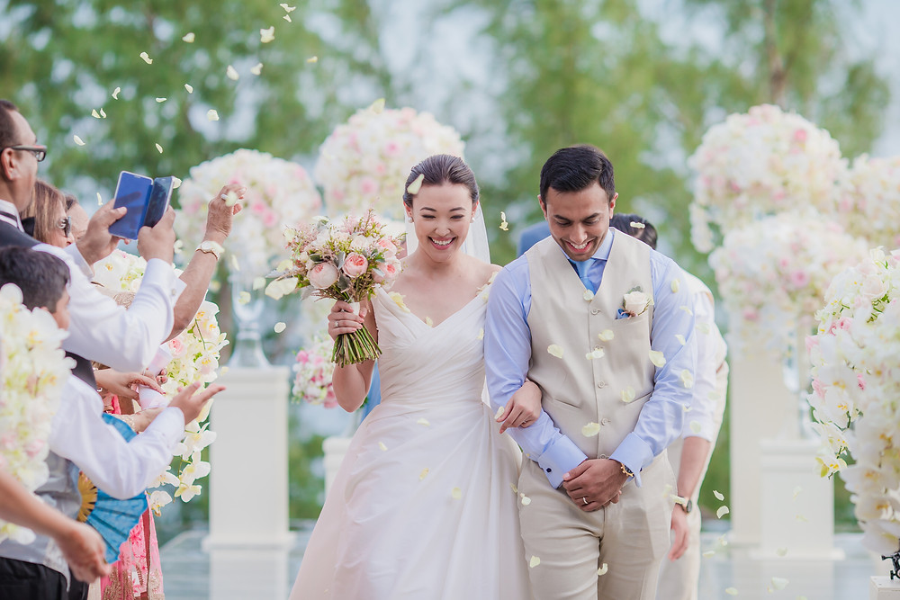 The Newlyweds receesed amid a shower of pink and peach rose petals