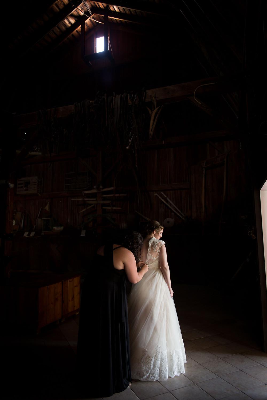 bride getting on dress in barn at Becker Farms Vizcarra Vineyards Gasport NY