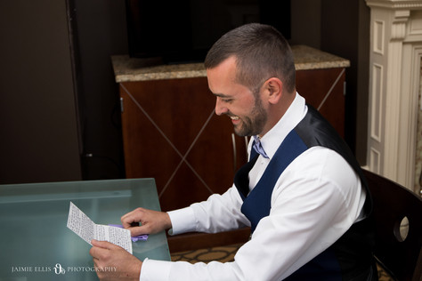 groom reading letter from him bride at Mansion on Delaware in Buffalo NY